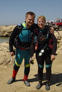 a young couple pose wearing diving equipment on their first scuba dive with a PADI Discover Scuba Diving Adventure in Cyprus