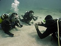 2 Divers practice new skills underwater with the scuba diving instructor
