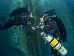 tdi normoxic trimix diver makes a no mask ascent under the gaze of instructor using the Zenobia wreck as a guide