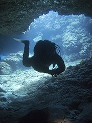 Diver silhouetted inside the cave at cyprus dive site, tunnels and caves