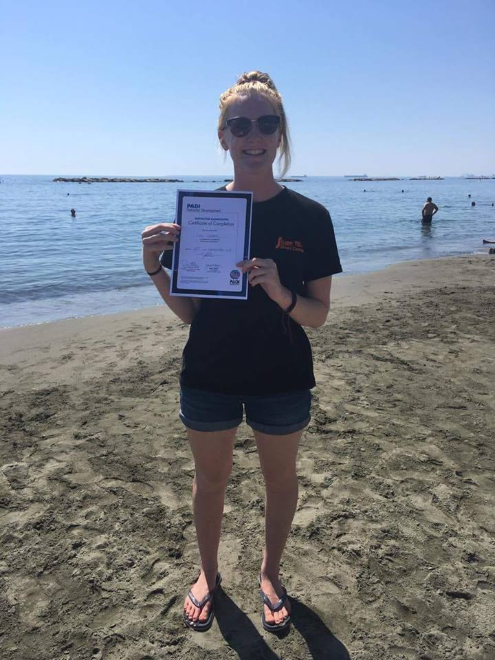 Lucy holds up her certificate from passing her PADI Instructor Exams here in Cyprus