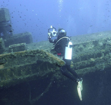 scuba diver with an underwater camera off the deck of the Zenobia shipwreck in Cyprus