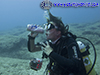 diver mimes drinking from a wine bottle found underwater